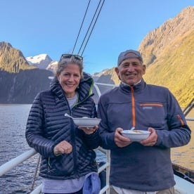 Couple having dinner on the boat at Milford Sound, Fiordland New Zealand