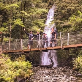 Group on the bridge at Hollyford track, Fiordland New Zealand