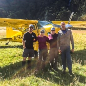 Group posing in front of the plane at Mount Aspiring National Park, West Coast New Zealand