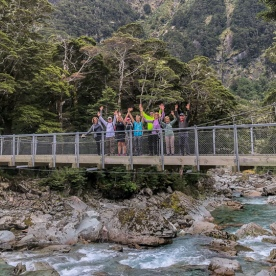 Group on the bridge at routeburn track river, Otago New Zealand