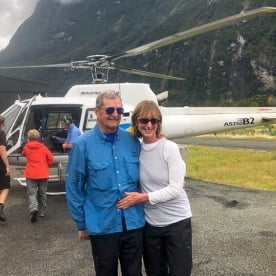 Couple with helicopter at Milford sound, Fiordland New Zealand