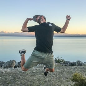 Guide jumping at Lake Pukaki with Aoraki Mt Cook in the background, Canterbury New Zealand