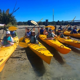The team excited for their kayaking trip on the Okarito Lagoon