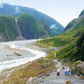 walkers on the track to fox glacier new zealand