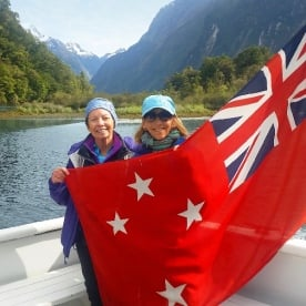 hikers holding new zealand flag at milford sound
