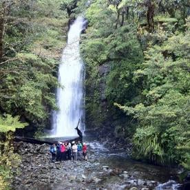Hiking group by waterfall and rainforest on the Hollyford Track