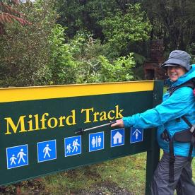 Happy hiker in rain by sign at end of Milford Track
