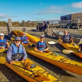 Group ready to kayak at Okarito Lagoon, West Coast New Zealand
