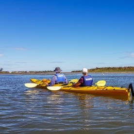 Couple kayaking at Okarito Lagoon, West Coast New Zealand