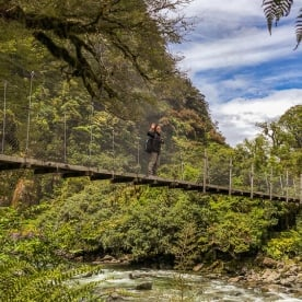 Passing bridge at at Hollyford track, Fiordland New Zealand