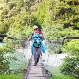 hiker crossing hollyford track bridge new zealand