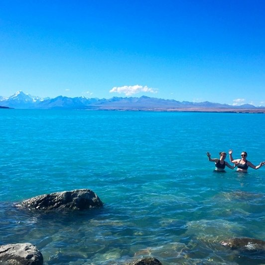 Having a dip in the glacial waters of Lake Pukaki. That's Aoraki/Mount Cook keeping watch!