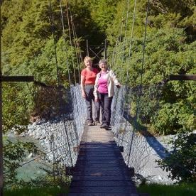 hikers crossing swingbridge on the hollyford track