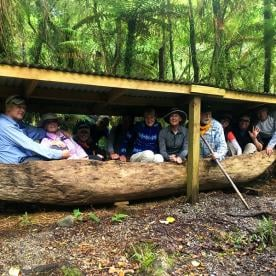 Group inside an antique Maori Boat